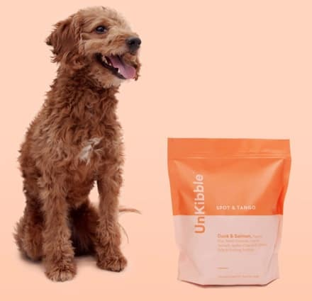 a happy dog sitting next to their Spot and Tango unKibble dog food